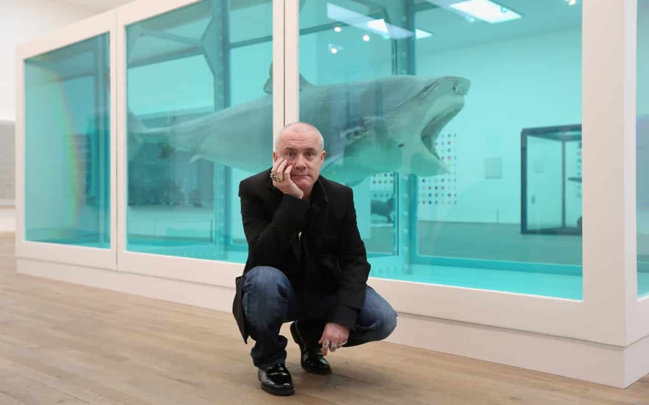 """Artist Damien Hirst in front of his artwork: The Physical Impossibility of Death in the Mind of Someone Living, 1991. Image source, article by Craig Raine """"Damien Hirst - pretty vacant"""" on newstatesman.com"""